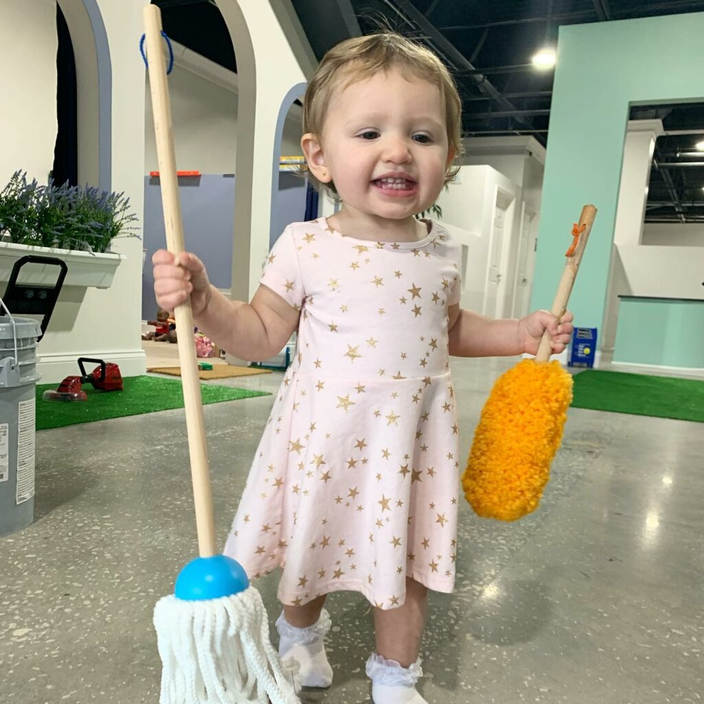 Child holding small mop and duster smiling